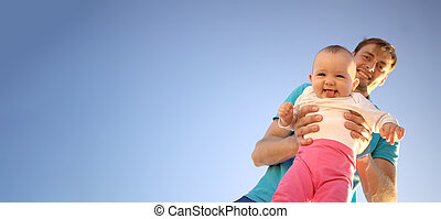 Father holds a small child in his arms on a background of a summer blue sky. Cute baby is smiling. Happy family outdoors.