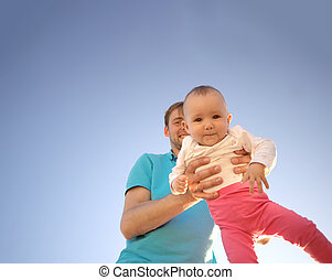 Father holds a small child in his arms on a background of a summer blue sky. Cute baby is smiling. Happy family outdoors