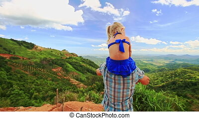 Father Holds Blond Daughter on Shoulders Wave against Valley