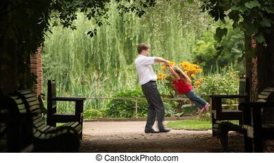 Father holds hands of his daughter and whirling her around...