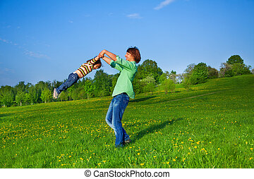 Father holds kid in the air while swirling him
