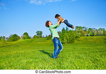 Father holds kid up above him in the air