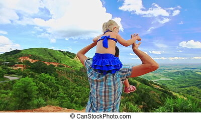 Father Holds Little Blond Daughter on Shoulders against Valley