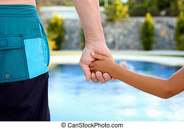 father holds the hand of a child