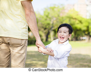 father holds the hand of little boy