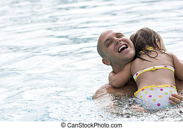 Father hugging young daughter in swimming pool
