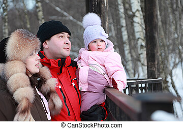 father hugs mother and little daughter looks into distance, winter, focus on girl