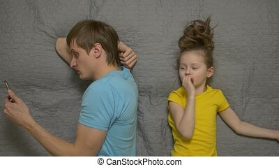 Father ignore his daughter daytime looking at smartphone addiction male 30 years old in blue t shirt caucasian white european lying on the bed disregard rejects does not communicate talking child little girl female caucasian white european 5 years old in yellow t shirt on gray sheet top view.