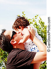 father in early thirties gives his son a kiss on the cheek in the park