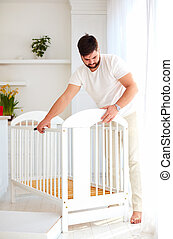 father installing the crib, preparing for a new baby in the family