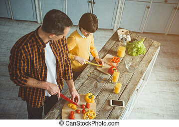Father instructing his son in kitchen
