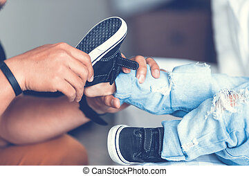 Father is helping his son to tie his shoes in the room on bed.