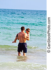 father is holding his son in the arms at the beautiful sandy beach
