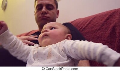 Father is immitating sounds that his six months old baby boy is making while tickling his feet. Baby is making funny faces and kicking with his feet