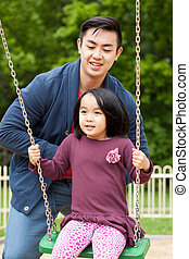 Father is playing on swing with her daughter