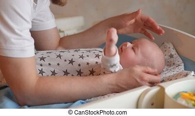 Father is playing with a small child. Dad spends time with a newborn baby