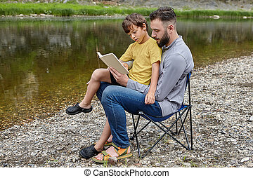 Father is reading a book to his son in nature.