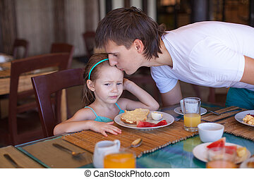 Father kiss his daughter before breakfast in the restaurant