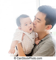 Father kissing baby boy.