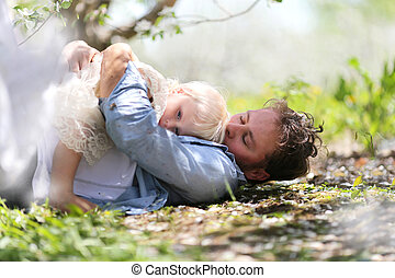 Father Kissing Baby Daughter Outside on Spring Day