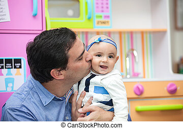 Father kissing his 6 months old baby girl
