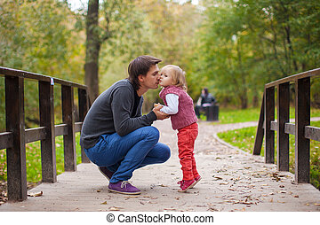 Father kissing his little daughter in a park