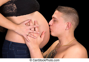Father kissing pregnant belly