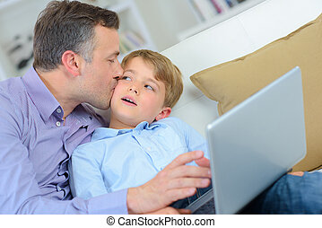 Father kissing son, holding laptop