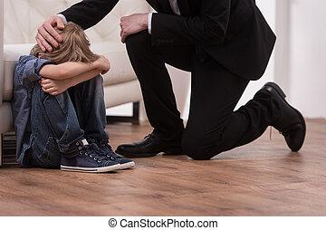 Father kneeling and comforts sad child. boy sitting on floor...