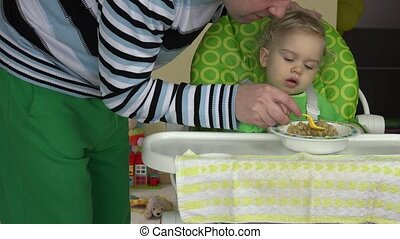 father learn baby girl eat gruel with spoon sit on highchair.