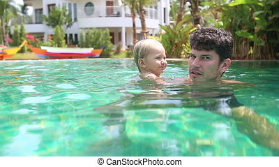 father learns swim daughter in swimming pool