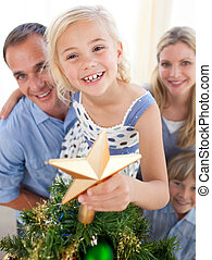Father lifting his daughter to put the Christmas star on top of the tree at home
