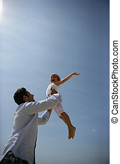 Father lifting his daughter up into the sky