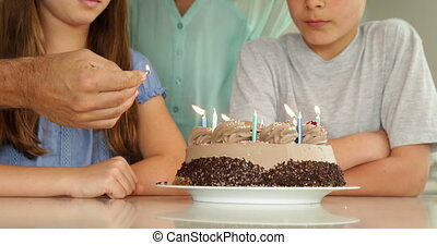 Father lighting candles on birthday cake