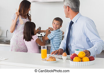 Father looking at his family cooking