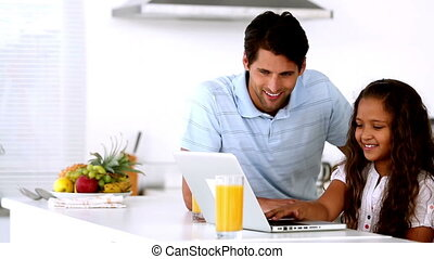 Father looking at laptop with his c