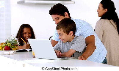 Father looking at laptop with son and mother enters to help daughter in the kitchen