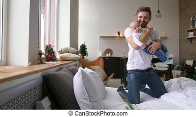 Father lying with cute baby daughter on bed at home