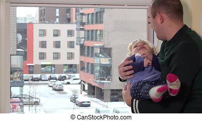 father man swing toddler daughter on his arms in front of window. Snow fall.