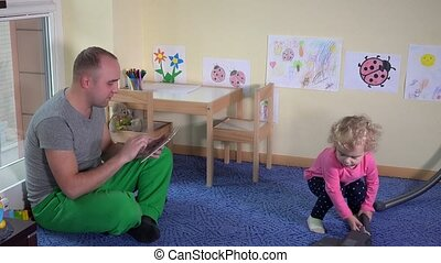 Father man using tablet computer and little daughter girl hoovering floor