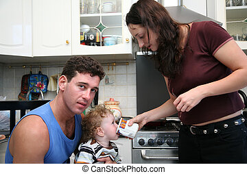 father, mother and child on the kitchen