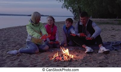 Father, mother and children warming by fire during evening...