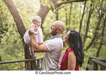 Father Mother and daughter baby in summer meadow park