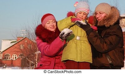 Father, mother and daughter playing outside with snow
