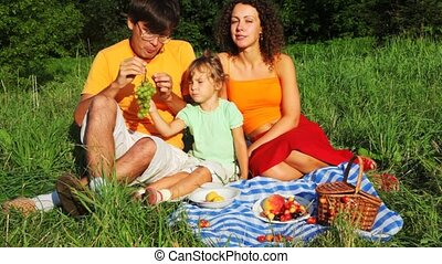 father, mother and daughter sits together on field near forest in park and eats fruit