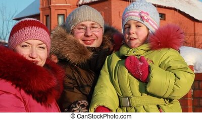 Father, mother and daughter standing outdoors in winter near house