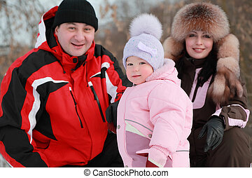 father, mother and little daughter at winter on nature, focus on girl