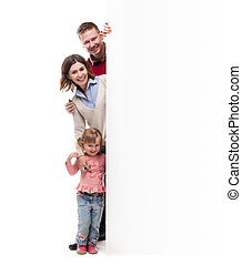 father, mother and little daughter peek out from behind empty blank
