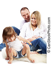 Father, mother and little daughter sit on the white hairy carpet, daughter tries to get up.