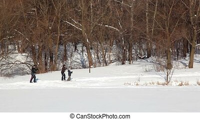 Father, mother and son skiing at winter day